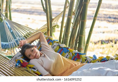 Editorial use only; a pretty lady relaxing on a bamboo hammock, in a park, at Pathumthani, Thailand, in January 2020.