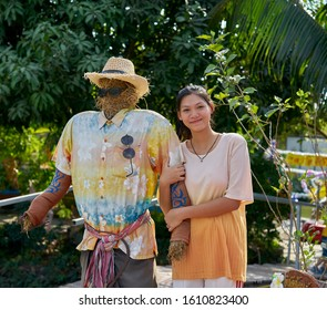 Editorial use only; a pretty Thai lady poses with a scarecrow, taken at Pathumthani, Thailand, in January 20202.