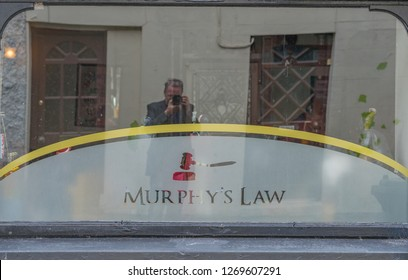 Editorial use only; a reflection of a photographer in a window, taken at Murphy's Law Bar, Athlone, Co. Westmeath, Ireland, in July 2017.