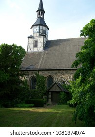Editorial use only; Schwichtenberg, Germany, May 21, 2009: Scenic view of a romanesque church surrounded by lush vegetation within the churchyard in Germany