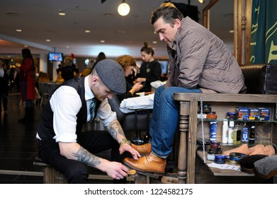 Editorial use only. Shoeshiner polishing client's boots with boot brush and blacking. Kiev, Ukraine. November 6, 2018