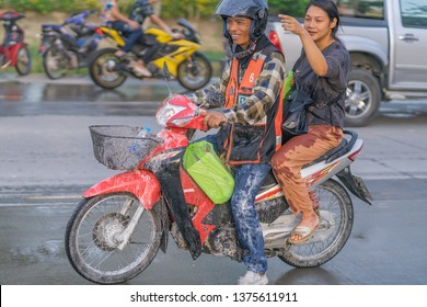 Editorial use only; a taxi motorcycle driver and passenger, travel during Songkran festival, at pathumthani, Thailand, in April 2019.