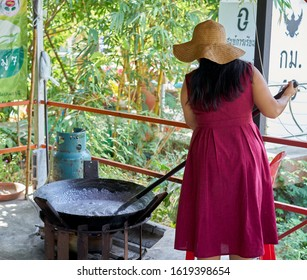 Editorial use only; a Thai lady, cooking candy in a large wok, this is how they make caramel, taken at Pathumthani, Thailand in January 2020.