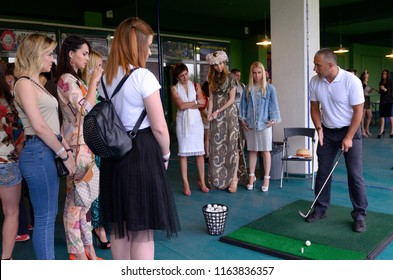 Editorial use only. Trainer stands with a golf club in hands teaching women golfing. Opening new golf club Golfstream. August 12, 2018. Kiev, Ukraine