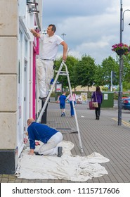 Editorial use only; two men painting a shop front, taken in Athlone, Co. Westmeath, Ireland, on July 11th, 2017.