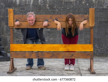 Editorial use only; two people in medieval stocks, at Athlone Castle, in Athlone, Co. Westmeath, Ireland, taken on July 12th, 2017.