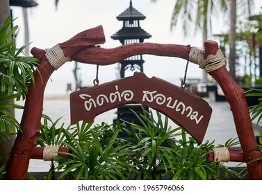 Editorial use only;  a wooden information sign in Thai script, with a tower in the background, taken at Phetchaburi, Thailand, in October 2020.