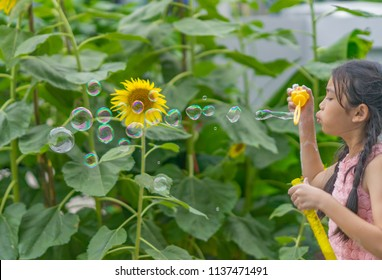 Editorial use only; a young girl blowing bubbles in a flower garden, taken at Pathumthani, Thailand, on July 18th, 2018.