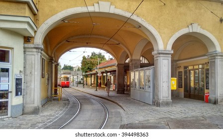 Editorial: Vienna, Austria, 16th August 2015. Entrance to tram and bus stop in Vienna's old historical quarter called 'Grinzing'. Old tram just leaving the station.