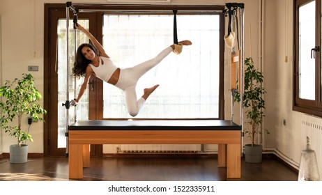 Editorial - Young woman exercising on pilates Cadillac. Pilates instructor stretching. Concept for pilates. 09/2019