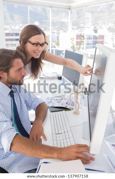 Editors reviewing photographs on computer at their desk in bright office