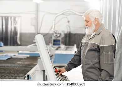 Edlerly bearded man operating laser plasma cutter on metalworking factory. Experienced engineer wearing in grey uniform working with computerized machine.