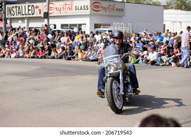 EDMONTON, AB, CANADA-July 18, 2014: Local News Anchor Gord Steinke riding on a motorcycle as seen in the K-Days Parade on July 18th, 2014.