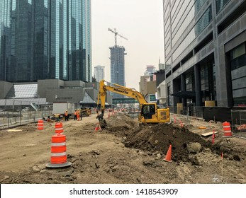 Edmonton, Alberta, Canada - May 30th, 2019: A large construction site in downtown Edmonton, Alberta with an excavator and construction workers continuing work on the light rapid transit line.