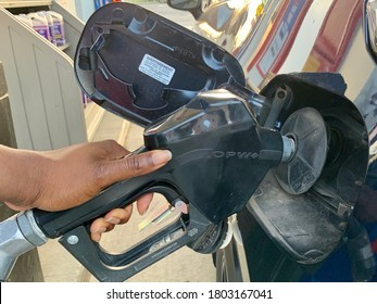 Edmonton, Canada - August 20, 2020: A Black person's hand on a nozzle pumping gas into her vehicle at a gas station
