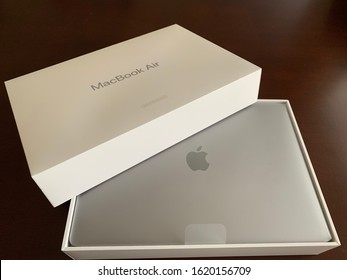 Edmonton, Canada - January 19, 2020: A top view of an Apple MacBook Air certified refurbished laptop and its box against a dark background