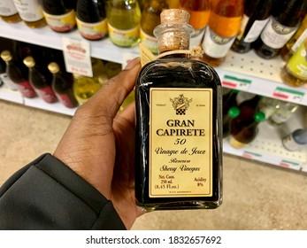 Edmonton, Canada - September 16, 2020: A Black person holding a bottle of Gran Capirete 50 Sherry Vinegar Reserve in a supermarket