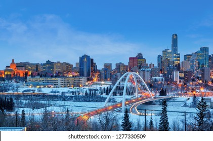 Edmonton downtown Winter sunset skyline showing Alberta Legislature and Walterdale Bridge across the frozen, snow-covered Saskatchewan River and surrounding skyscrapers. Edmonton is Alberta' capital.