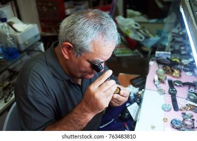 Edremit, Turkey - August 21, 2017: Traditional watchmaker  repairs a watch with magnifier in Edremit, Turkey.