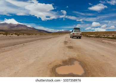 Eduardo Avaroa National Park, Bolivia, February 2018: offroad vehicle driving in the wilderness of Andean mountains covered in snow