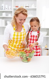 Educating kids for healthy lifestyle choices - mother and young daughter preparing vegetables salad together