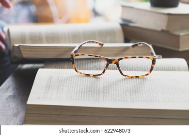 Education , Academic and Learning concept background idea. Glasses on opening book in library or cafe.