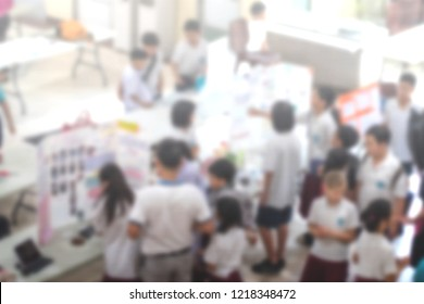 Education back to school background concept. Blurred students science class exhibition display board in school hall with schoolboy and schoolgirl and teacher.