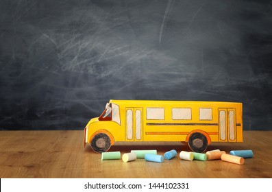 education and back to school concept. cardboard bus and chalks in front of classroom blackboard