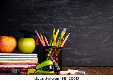 Education or back to school Concept. Colorful school supplies with books, color pencils, calculator, pen cutter clips and green apple on chalkboard background.