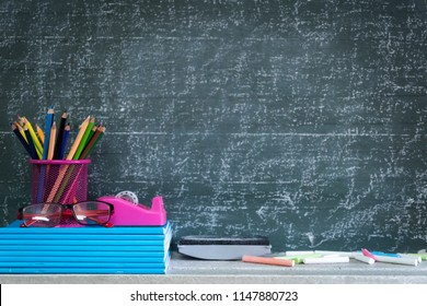 Education or back to school Concept. glasses, pencils, note books, chalk, eraser over chalkboard background.