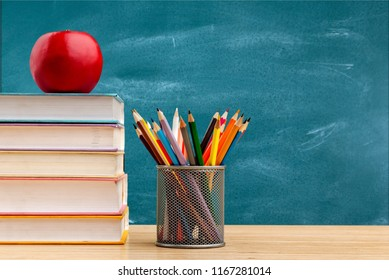 Education or back to school Concept. glasses, pencils, note books, chalk, eraser over chalkboard background.