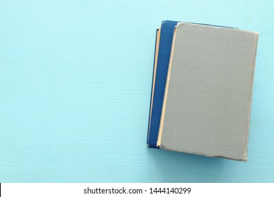 education and back to school concept. stack of books over wooden blue background. top view, flat lay