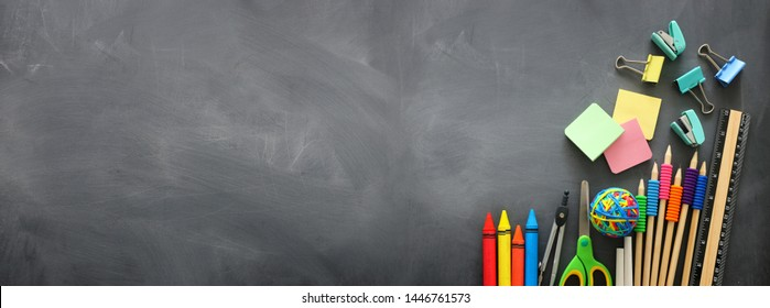 education and back to school concept. stationery over classroom blackboard. top view, flat lay