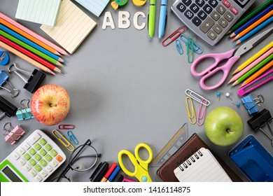 Education or back to school Concept. Top view of Colorful school supplies with books, color pencils, calculator, pen cutter clips and green apple on gray background. Flat lay.