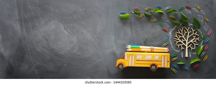 education and back to school concept. Top view photo of bus and pencils on the roof next to tree with autumn leaves over classroom blackboard background. top view, flat lay