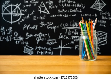 Education background concept. Stationery in glass jar color pencil, compasses tool, scissors, rulers, sharpener On chalkboard with the Mathematical formula background.