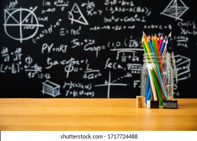 Education background concept. Stationery in glass jar color pencil, compasses tool On chalkboard with the Mathematical formula background.