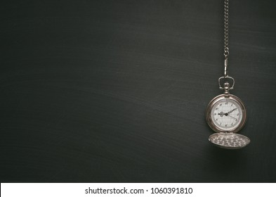 Education background with copy space. Pocket watch on blackboard surface background with copy space.