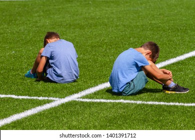 education, bullying, conflict, social relations and people concept - two sad disappointed boys sitting back to back on the grass in stadium