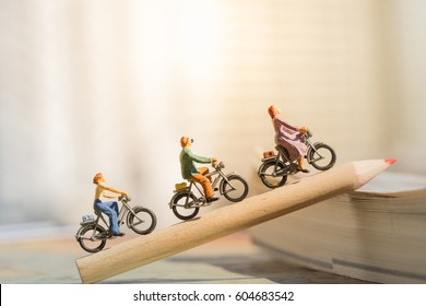 Education and Business concept. Miniature people : Small figures cycling on red color pencil using as background.