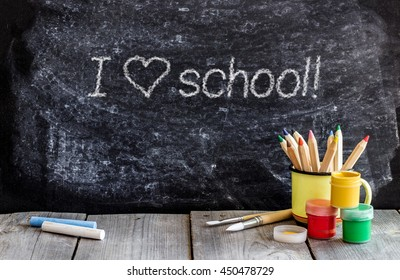 Education and business concept. School chalkboard with text, crayons, chalk and paint on a wooden table. Selective focus, copy space background