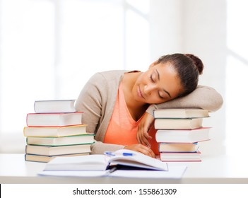 education and business concept - tired student with pile of books and notes studying indoors
