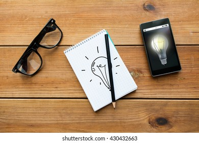 education, business, idea and technology concept - close up of light bulb drawing in notepad with pencil, smartphone and eyeglasses on wooden table