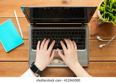 education, business, people and technology concept - close up of woman or student typing on laptop computer with notebook and earphones on wooden table