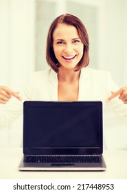 education, business, technology and internet concept - smiling woman with laptop pc