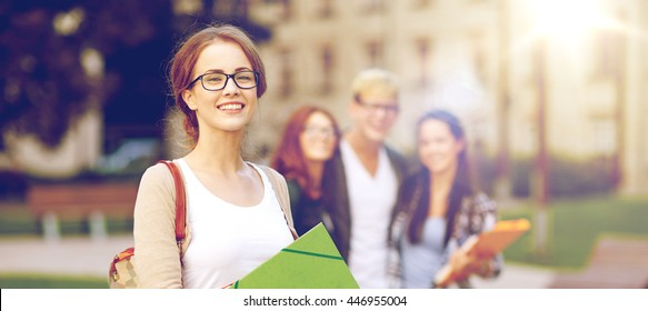 education, campus, friendship and people concept - group of happy teenage students with school folders