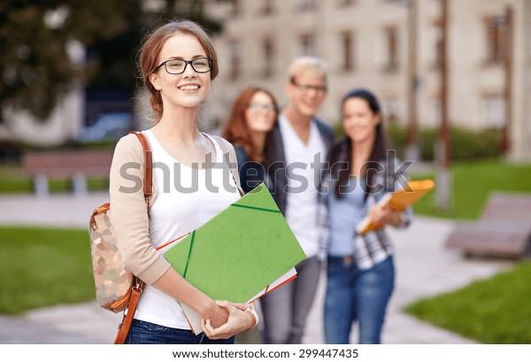 Bildungs-, Campus-, Freundschafts- und People-Konzept - Gruppe glücklicher Jugendlicher mit Schulordnern