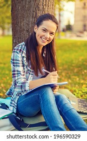 education, campus and people concept - smiling teenager writing in notebook