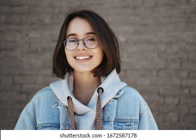 Education, career for young people concept. Close-up portrait of happy smiling 20s girl in glasses and denim jacket over hoodie, look camera satisfied and cheerful, stand outside over brick wall