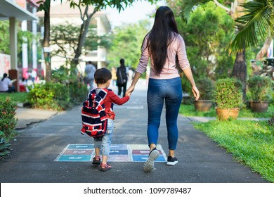 Education, childhood, family and people concept. Mother and her little son walking together going to the school.